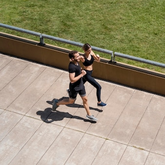 High angle of man and woman jogging together outdoors
