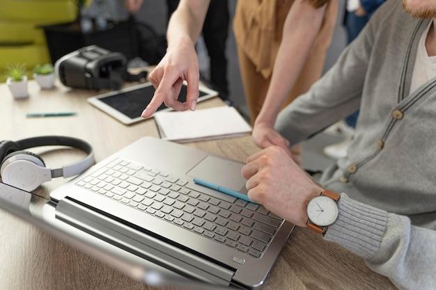 Alto angolo di uomo e donna che lavorano con laptop e cuffie