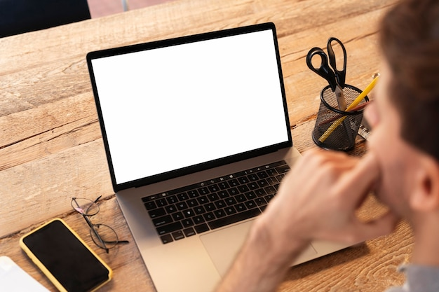 Человек под высоким углом, работающий над внештатным проектом на ноутбуке
