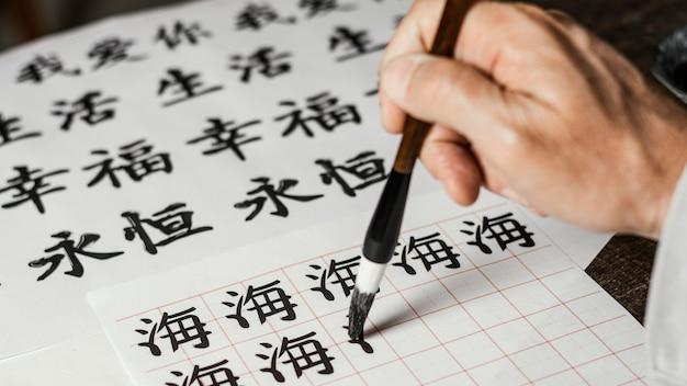 High angle man writing chinese symbols on white paper