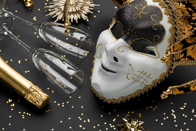 High angle of mask for carnival with glitter and champagne glasses