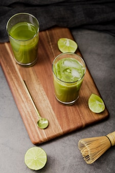 High angle of matcha tea in glasses with lime