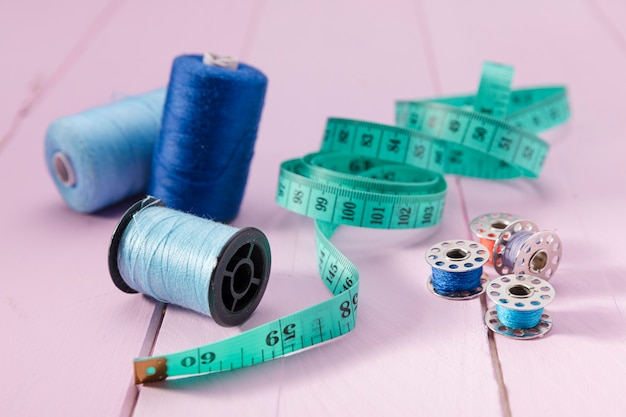 High angle of measuring tape with thread reels and sewing machine shutles