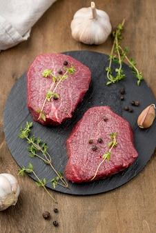 Alto angolo di carne su ardesia con erbe e aglio