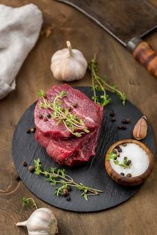 Alto angolo di carne su ardesia con erbe