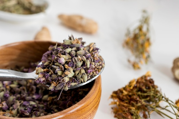 High angle of medicinal herbs in bowl with spoon