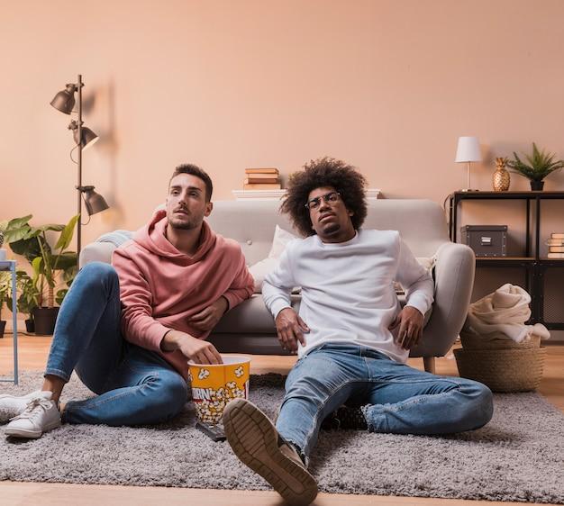 High angle men on floor eating popcorn