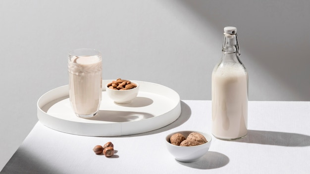 High angle of milk bottle with glass on tray and walnuts