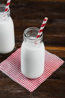 High angle milk bottle with straw on table