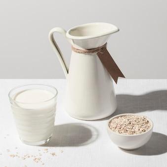 Alto angolo di bicchiere di latte con brocca e ciotola di farina d'avena