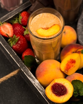 High angle of milkshake glass with peach and strawberries