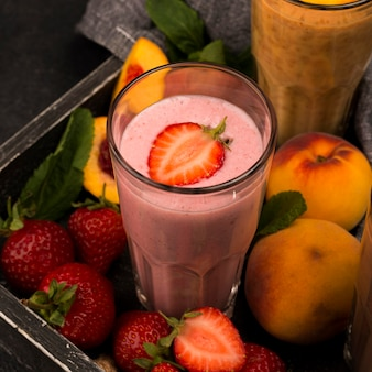 High angle of milkshake glass with strawberry and peaches
