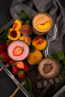 High angle of milkshake glasses on tray with fruits and chocolate