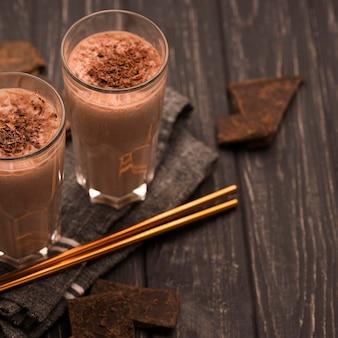 Alto angolo di bicchieri da milkshake con cannucce e cioccolato