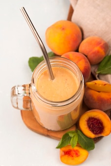 High angle of milkshake with peaches and metal straw
