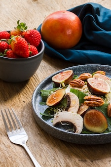 High angle mix of figs and nuts on plate with strawberries