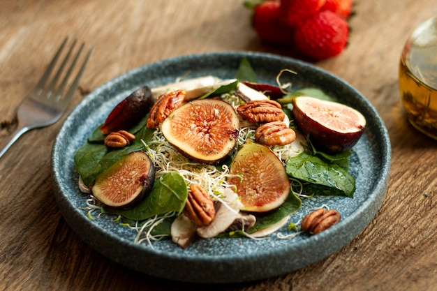 High angle mix of nuts and figs on plate with strawberries