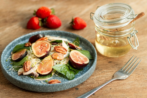 High angle mix of nuts and figs with strawberries on plate with honey