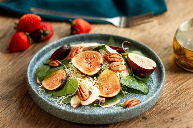 High angle mix of nuts and figs with strawberries on plate