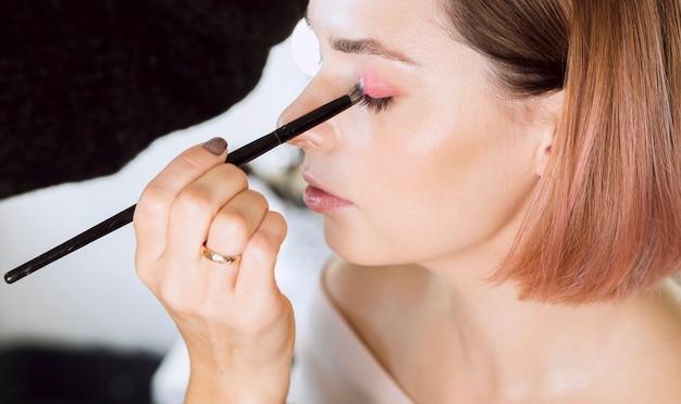 High angle model applying eyeshadow