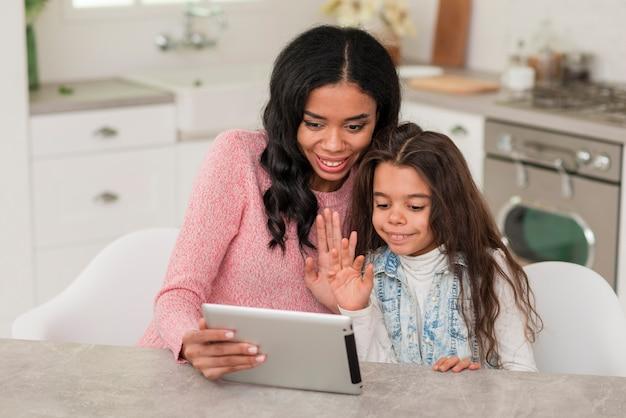 Высокий угол мама и дочь с помощью планшета