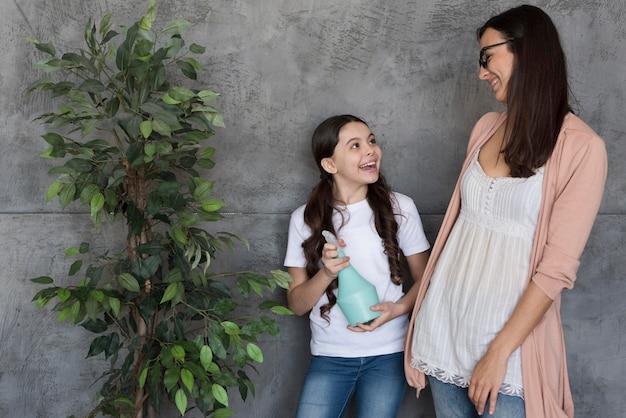 Высокий угол мама и девушка полива растений
