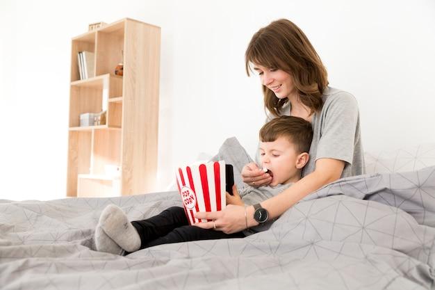 High angle mom feeding her son popcorn