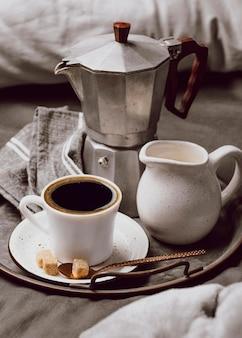 Alto angolo di caffè del mattino sul letto con latte e bollitore