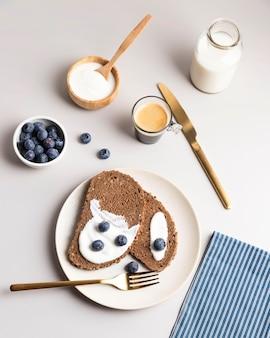 Alto angolo di pane tostato mattutino con mirtilli e latte