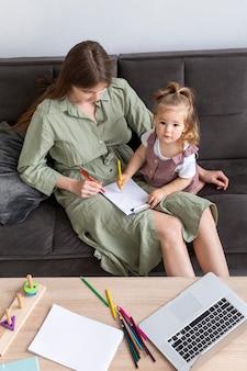 Высокий угол мать и ребенок на диване