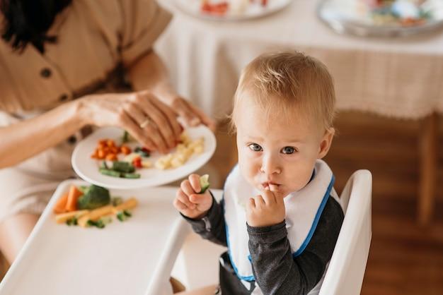 Мать под высоким углом помогает ребенку выбрать, какую еду съесть