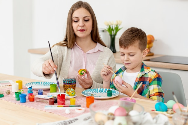 High angle mother and son concentrated to paint eggs