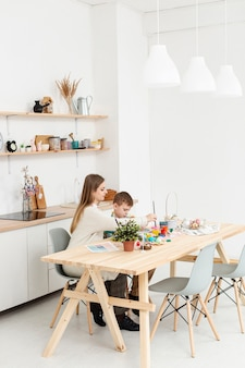 High angle mother and son at home painting eggs