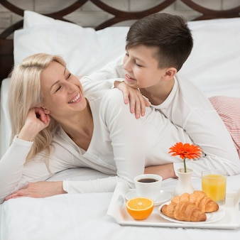 High angle mother surprised in bed with breakfast