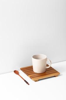 High angle of mug on coaster with spoon and copy space