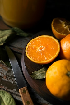 High angle of multiple autumn oranges with knife