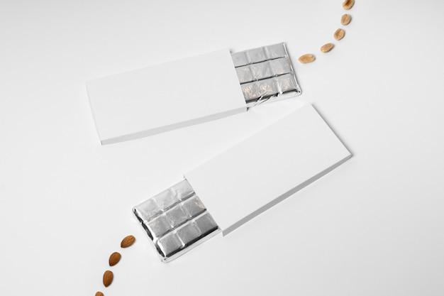 Alto angolo di più pacchetti vuoti di barrette di cioccolato con pellicola e noci