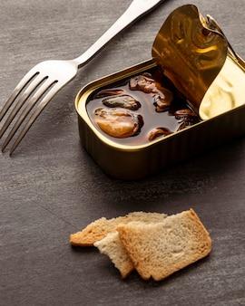 Barattolo di latta di cozze ad alto angolo con pane tostato e forchetta