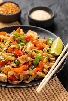 High angle noodles with vegetables and chicken with chopsticks