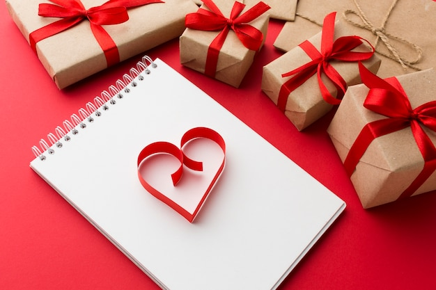 High angle of notebook with paper heart shape and presents