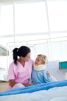 High angle of a nurse and her patient sitting on a hospital bed
