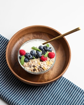 High angle of oatmeal bowl with raspberries and blueberries