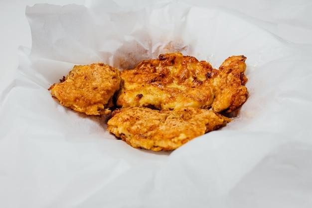 스튜디오의 흰색 배경에 있는 그릇에 냅킨에 배터에 구운 닭고기의 식욕을 돋우는 높은 각도