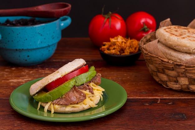 Высокий угол арепы на тарелке с помидорами