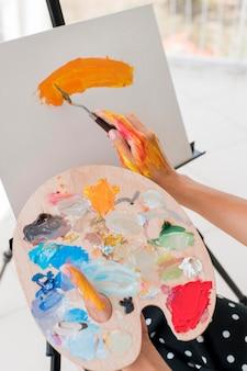 Высокий угол живописи художника с палитрой