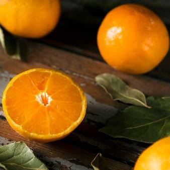 Высокий угол осенних апельсинов с листьями