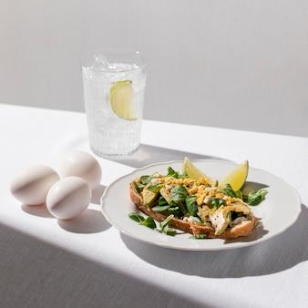 Тост с авокадо под высоким углом на тарелке с яйцами и стаканом ледяной воды