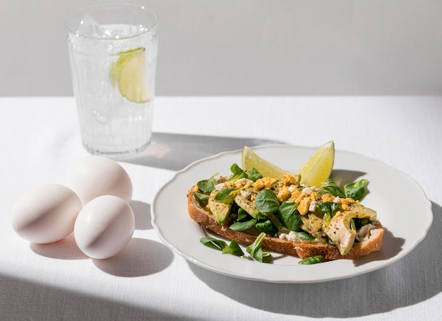 얼음 물과 계란의 유리와 함께 접시에 아보카도 토스트의 높은 각도