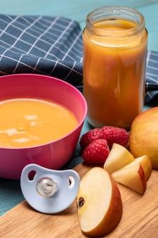 Высокий угол детского питания в миске с яблоками и соской