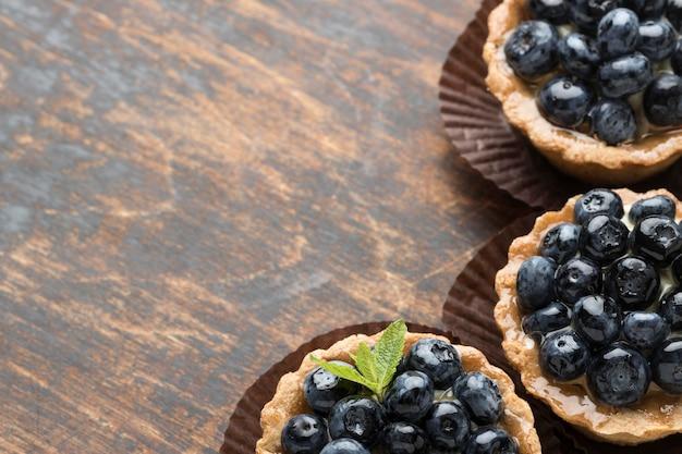 Высокий угол черничных десертов с мятой и копией пространства